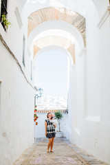 Woman and baby stand underneath spanish white arch