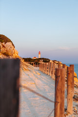 sunset on a hiking path and lighthouse in the algarve of portugal