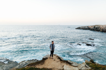 man standing on a rock and looking at the sea