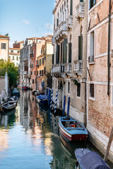 lots of tied up boats along a canal in venice italy