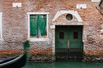 green door and bricks as a gondola passes in venice italy