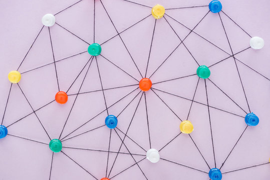 top view of push pins connected with strings Isolated On pink, network concept