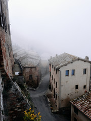 morning fog over tuscan town