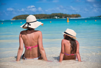 Mother and daughter talking on a beautiful beach, sitting on the water edge, view from the back