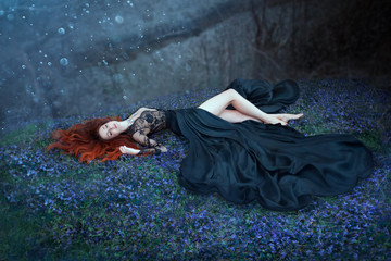 girl with red hair lying on grass in dark forest, black queen lost in battle, charming lady in long black royal dress with lace on open chest, sexy hot nymph with long bare legs in highlights of moon