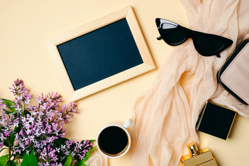 Female workspace with photo frame, sunglasses, silk scarf, coffee cup, accessories, perfume bottle, lilac flowers on beige background. Flat lay women's office desk. Top view feminine background.