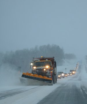 Snowplow clearing away drifting snow on Ontario highway in January 2019 at dusk with long line of vehicles following behind