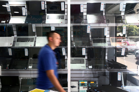 A man walks in front of a showcase displaying computers at a store in Mexico City,