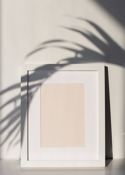 White Picture Frame with Matting on a Shelf with a Palm Tree Leaf Shadow, White Background. Poster and Print Design Photo Mock-Up, Blank and Empty Frame - 12x16 inches, 8x10 inches or Similar Ratio