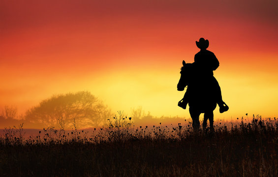 cowboy riding in the hills at sunset