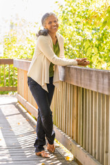 Happy, smiling, mature African American black woman outdoors. Healthy senior lifestyles.