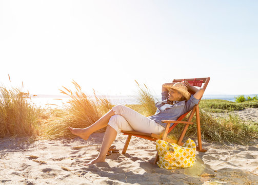 Happy, middle-aged, black, African American woman relaxing on the beach in summer. Healthy mature lifestyles.