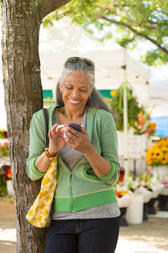 Happy, mature, black, African American woman texting with  cell phone at farmers market. Seniors using mobile technology.