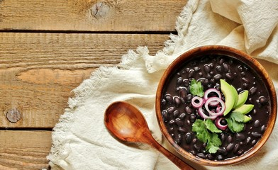 thick black bean soup or stew. Latin American or Mexican cuisine. stewed black beans served with avocado and red onion and cilantro. place for text. top view.
