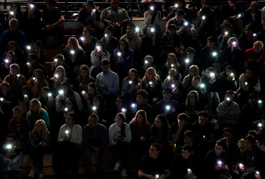 People hold up their phone lights during a moment of silence at a vigil for the victims of the shooting at the Science, Technology, Engineering and Math (STEM) School in Highlands Ranch