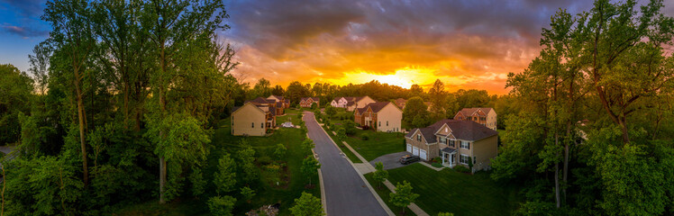 Fototapeta Aerial panorama of a modern row of newly constructed two story single family homes in a new construction middle class neighborhood street in the USA - American real estate with dramatic sunset sky obraz