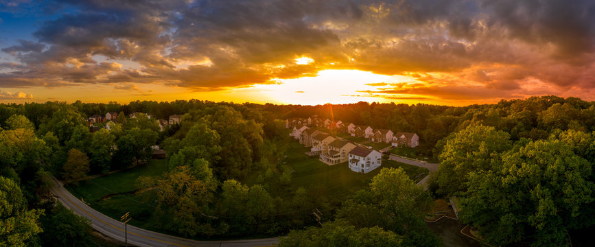 Aerial panorama of a modern row of newly constructed two story single family homes in a new construction middle class neighborhood street in the USA - American real estate with dramatic sunset sky
