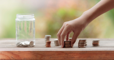 Closeup for hand Little girl picking up pile coin for saving money into piggy bank for future life. Investment and Saving Concept.