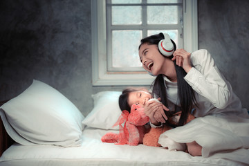 Sister and daughter are lying on bed and playing; happy loving family for relationship at home.