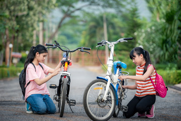 Little two girls prepare back to school after the school long holidays with bicycle, primary education level, education concept.