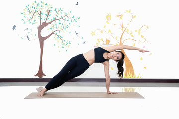 healthy women practicing yoga in gym . standing stretching in Tree pose,concept for exercising and health care indoor.