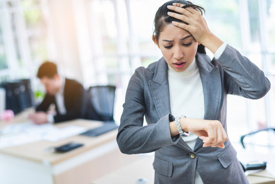 Young attractive Asian business woman looking at the watch time worried and afraid of getting late to meeting with boss or customer.