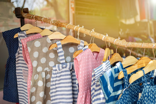 Kids's fashion, cute little girl dress hanging on wooden stick over blurred cloth shop background