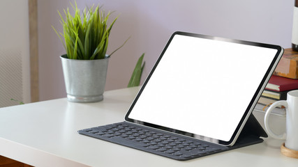 Mockup tablet computer and blank screen on workspace