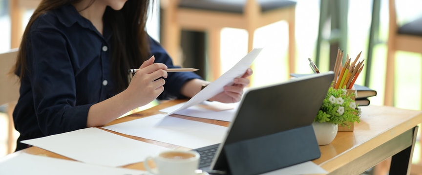 Freelancer woman working with paperwork on desk in co-working space