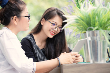 two asian woman with smart phone in hand talking  in home living room with happiness face