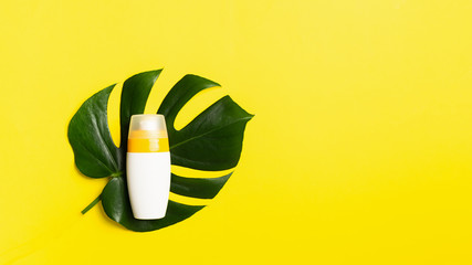Sunscreen in a bottle large sheet of tropical plants on a bright yellow background. Summer holiday concept and beach.