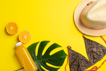 Summer beach accessories hat swimsuit bottle of orange juice bright yellow background big green leaves tropical plant.