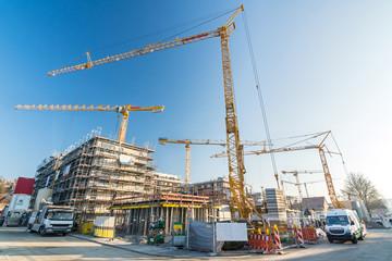 Weitwinkelaufnahme von Baustelle und Rohbau von Büros und Mehrfamilienhäusern mit vielen Kränen und Baufahrzeugen