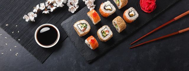 Foto op Plexiglas Sushi bar Set of sushi and maki rolls with branch of white flowers on stone table