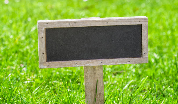 Empty sign on a green lawn