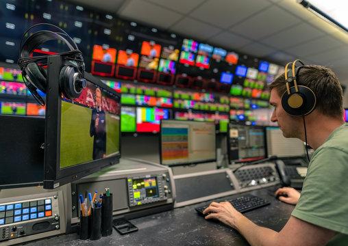 Arbeiten beim Fernsehen, Mann mit Kopfhörern vor Monitoren