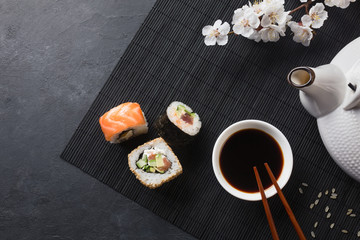 Foto op Aluminium Sushi bar Set of sushi and maki rolls with branch of white flowers and teapot on stone table