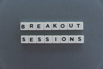 Breakout Sessions word made of square letter word on grey background.
