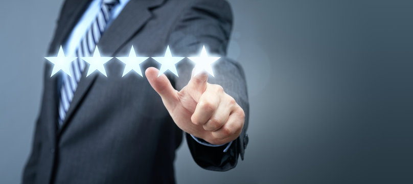 Businessman pointing to five star service rating symbol