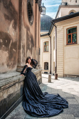 Princess in black dress, stands against wall, an ancient building, Lviv, Ukraine