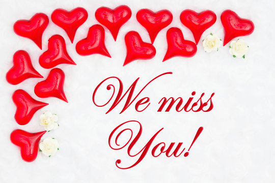 We miss you message with red hearts on white fabric