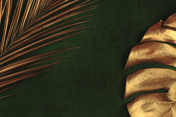 Closeup of golden palm and monstera leaves on abstract dark green textured background. Tropical conceptual elegant trendy summer background. Flat lay. Copy space. Wall mural