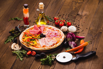Italian Four Seasons Pizza (Quattro Stagioni) on the wooden background with ingredients around (close)