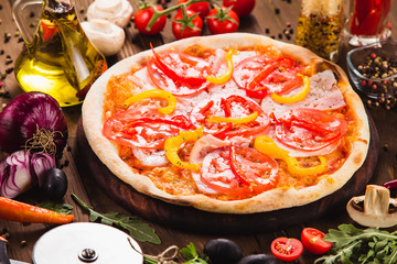Venice pizza with ham, tomatoes and paprika on a dark wooden background with ingredients around (close)