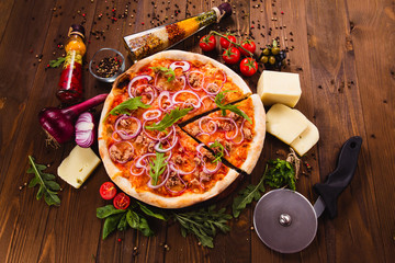 Italian pizza with chicken, onions and rucola leaves on a dark wooden background with ingredients around (close top view). Cut one piece