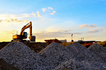 Heavy excavator bucket working in quarry on a background of sunset and blue sky. Mobile jaw stone crusher by the construction site. Crushing old concrete wastes and subsequent cement production Wall mural