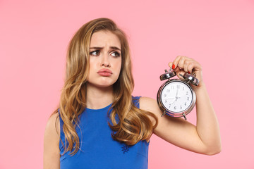 Displeased young pretty woman posing isolated over pink wall background holding alarm clock.