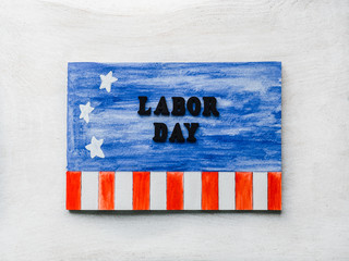 LABOR DAY. Notepad, American flag pattern and wooden letters of the alphabet on a white table. Close-up. Bright photo and space for your inscriptions. Congratulations to relatives, friends, colleagues