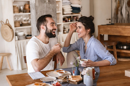 Image of modern brunette couple eating breakfast together while sitting at table at home