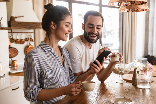 Photo of european brunette couple drinking coffee and using cell phone during breakfast in kitchen at home